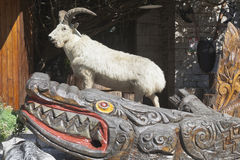 Sculptural composition of a stuffed goat and carved wooden crocodile at the foot of the tower on a mountain Big Ahun, Sochi Stock Photo