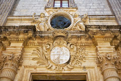 Sculptural decoration over the entrance to Palazzo Vilhena, now. Decoration with the coats of arms and bas-relief of Antonio de Vilhena over the entrance to Stock Photos
