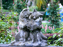 Sculptural group - the cat family of gray stone in the garden Royalty Free Stock Image