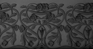 Sculptural relief with floral decoration. Shot in black and white detail on the sculpture on the facade of this historic building representing some characters / stock images
