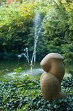 Sculpture. Stone sculpture with fountain near small lake Stock Images