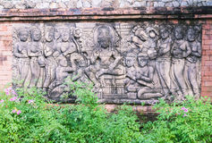 Sculpture about the ancient Cambodian King surroundinin women on wall in garden. Sculpture on wall in botanic garden, Thailand. It is about the ancient King Stock Images