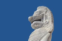 Sculpture of ancient white stone singha statue isolated on blue sky Royalty Free Stock Photography