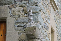 Sculpture of angel defeating the enemy on the background of a stone building in Rupit. Catalonia, Spain Stock Photos