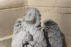The sculpture of angel with hands joined in silent prayer stock photo