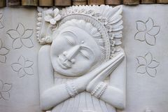 Sculpture of a balinese sleeping woman in silence stock photo