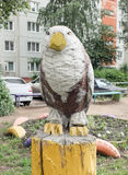 Sculpture of a bird of prey sitting on a stump Royalty Free Stock Photography