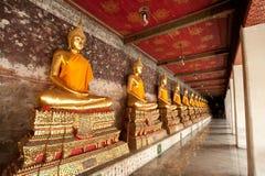 Sculpture bouddhiste d'or dans l'action de méditation devant le vieux mur de briques Photographie stock libre de droits