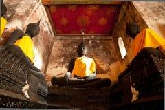 Sculpture bouddhiste dans l'action de méditation devant le vieux mur de briques Photo libre de droits