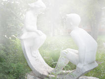 Sculpture of the boy and the girl in the foggy morning Stock Photo
