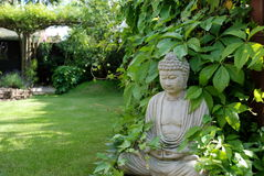 Sculpture of Buddha. In back yard against a background of green leaves Stock Images