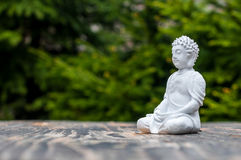Sculpture of Buddha become enlightened on green background. Yoga and meditation concept Stock Photography