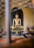 Sculpture of Buddha which is behind bars. royalty free stock image