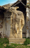 Sculpture and building ruins. Mythical stone sculpture with building ruins in background stock image