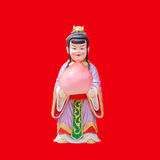 Sculpture china doll holging a peach on red Royalty Free Stock Photography