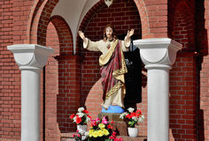 Sculpture of Christ in the arch of red church. Stock Photos