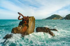 Sculpture `The Comb of the Wind` in Donostia, the Basque Country of Spain. Sculpture `The Comb of the Wind` with scenic waves  at the western end of the Bay in Royalty Free Stock Photo