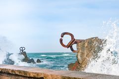 Sculpture `The Comb of the Wind` in the Basque Country of Spain. Sculpture `The Comb of the Wind` with giant scenic waves  at the western end of the Bay in the Royalty Free Stock Images