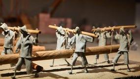 Sculpture composition, people carry log, symbol hard work stock image