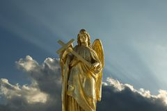 Angel with cross in his hands. Sculpture of contemplating golden angel with cross royalty free stock photography