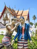 Sculpture of couple of Burmese lovers in a whispering manner with famous Wat Phumin buddhist temple in the background in Nan city. Thailand stock photography