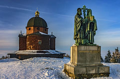 Sculpture Cyril and Methodius. Church on a background on top of the mountain Radhost in winter royalty free stock images