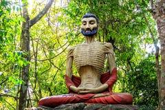 Sculpture d'un yoga ascétique dans la méditation dans une forêt tropicale photographie stock