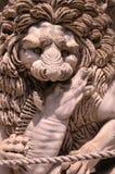 Sculpture d'une tête médiévale de lion de la pierre qui maintient la proie dans ses pattes Italie image libre de droits