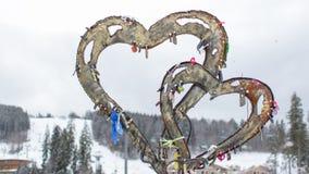 Sculpture de deux coeurs de fer avec des serrures des amants Photos stock