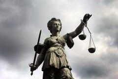 Sculpture de Justizia avec les nuages foncés Photo libre de droits