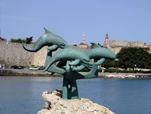Sculpture of a dolphin jumping on a rock in front of the harbor of Rhodes, Greece. Big sculpture of a dolphin jumping on a rock in front of the harbor of Rhodes royalty free stock image