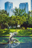 Sculpture of dolphins in the city park on the background of buildings. City art. Kuala Lumpur, Malaysia. Royalty Free Stock Images