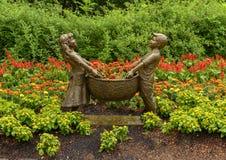 Sculpture en bronze d'un garçon et d'une fille tenant un panier par Gary Price à Dallas Arboretum et au jardin botanique photos libres de droits