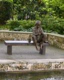 Sculpture en bronze d'un garçon sur un banc pêchant par Gary Price à Dallas Arboretum et au jardin botanique photos libres de droits