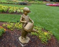 Sculpture en bronze d'un gar?on avec une bo?te et une sauterelle d'arrosage par Gary Price ? Dallas Arboretum et au jardin botani images libres de droits