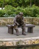 Sculpture en bronze d'un vieil homme pêchant par Gary Price à Dallas Arboretum et au jardin botanique photographie stock libre de droits