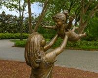 Sculpture en bronze de femme supportant un enfant heureux par Gary Price à Dallas Arboretum et au jardin botanique images libres de droits