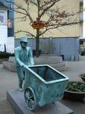 Sculpture en bronze de l'homme poussant le chariot vide Photographie stock libre de droits