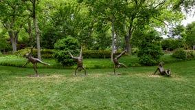 Sculpture en bronze des enfants faisant des roues par Gary Price à Dallas Arboretum et au jardin botanique photos stock