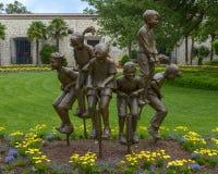 Sculpture en bronze des enfants sur des b?tons de pogo par Gary Price ? Dallas Arboretum et au jardin botanique image libre de droits