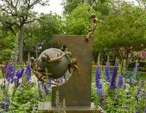 Sculpture en bronze des enfants volant autour de la terre par Gary Price à Dallas Arboretum et au jardin botanique images stock