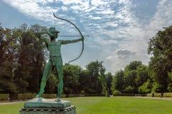 Sculpture en bronze verte en archer dans un jardin d'herbe verte Image libre de droits