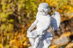 Sculpture en pierre Un dieu grec de l'amour sur le fond brouillé Images stock