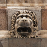 Sculpture of a fierce lion muzzle. Ancient sculpture of a fierce lion muzzle stock photo