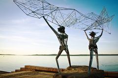 Sculpture of fishermen on the waterfront. throw a net in the sea. Russia. Petrozavodsk-July 2014. Sculpture of fishermen on the waterfront. throw a net in the Stock Images