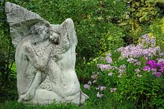 Sculpture and flowers of Phlox in the city garden royalty free stock images