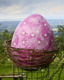 Sculpture of a giant pink easter egg in a basket Stock Photos