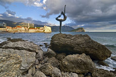 Sculpture girl dancing. Against the backdrop of the old town of Budva. Montenegro Royalty Free Stock Images