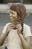 Sculpture of a girl eating called Stock Photography
