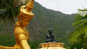 Sculpture of a golden angel against the background of the Thai Wat. Statue of a sitting black monk. Part of the public temple complex at the foot of the mountain stock video